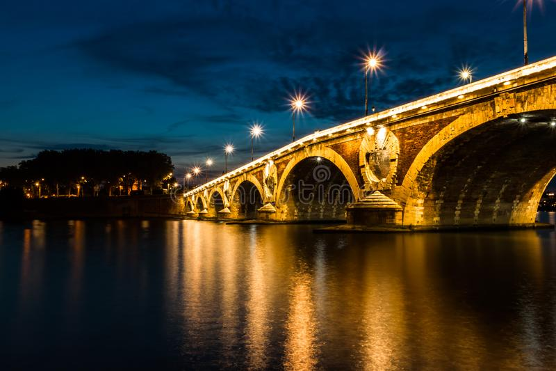 Upplyst bro på skymning, Toulouse, Frankrike royaltyfria bilder