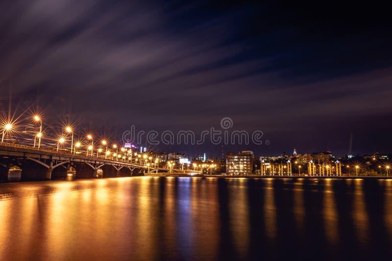 Upplyst Chernavsky bro på natten, sikten till den högra banken eller centret av den Voronezh staden, dramatisk cityscape med refl arkivbilder
