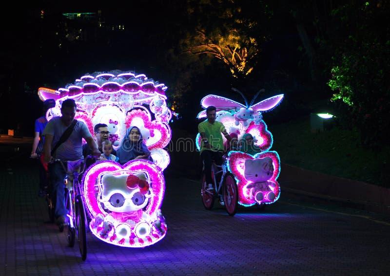 Upplyst dekorerad trishaw med mjuka leksaker på natten i Malacca, Malaysia arkivfoton