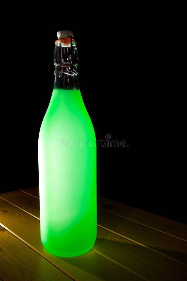 Upplyst drinkflaska för grönt exponeringsglas Konsthantverk som återanvänder pr arkivbild