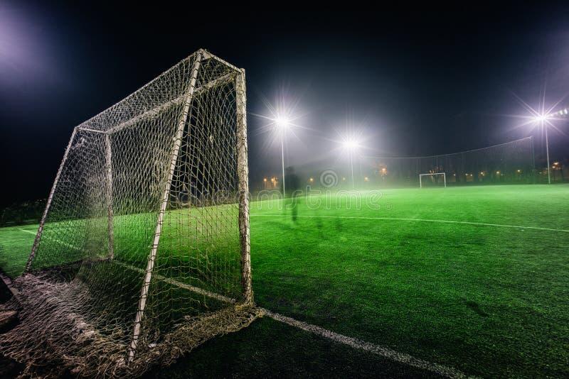 Upplyst fotbolllekplats med grönt gräs royaltyfria bilder