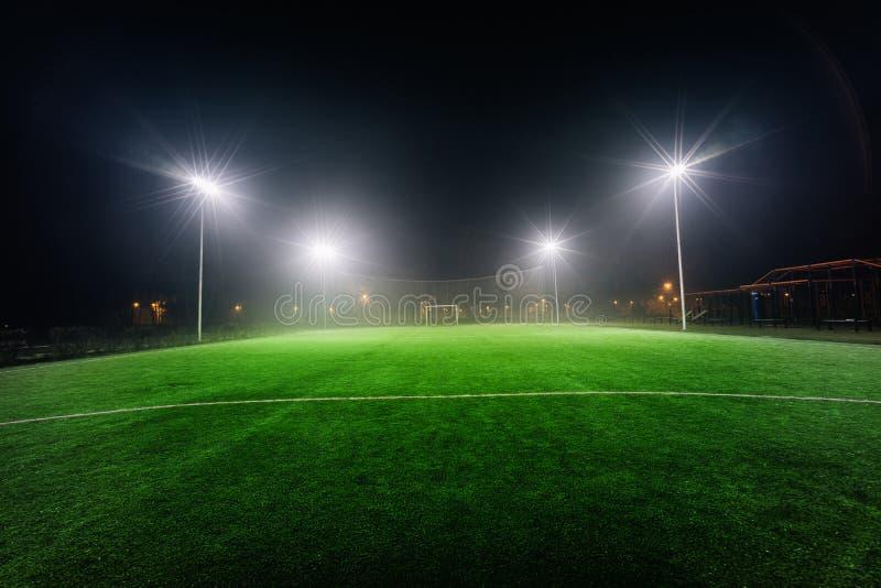 Upplyst fotbolllekplats med grönt gräs fotografering för bildbyråer