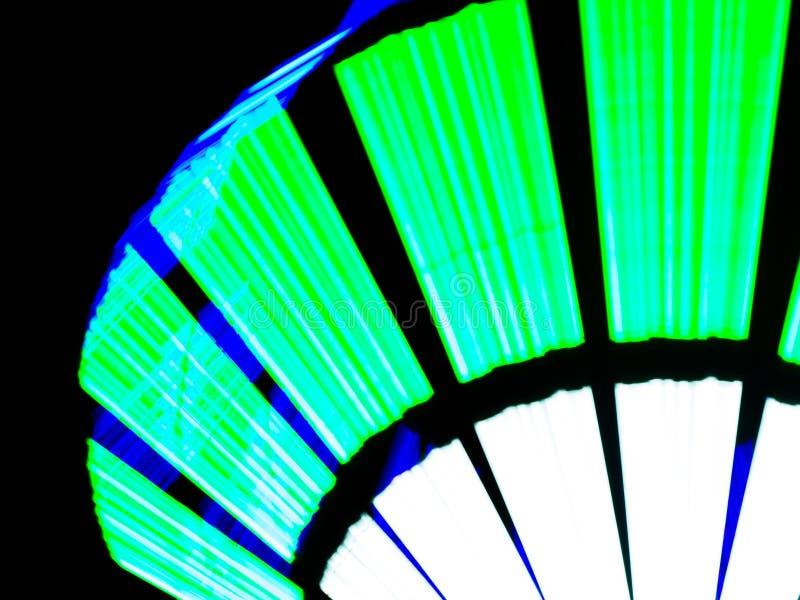 Upplyst grön design för neonljus vid lång slutarehastighet royaltyfria foton