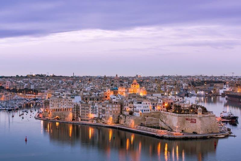 Upplyst horisont av Senglea på twilighsolnedgången, Malta arkivfoton