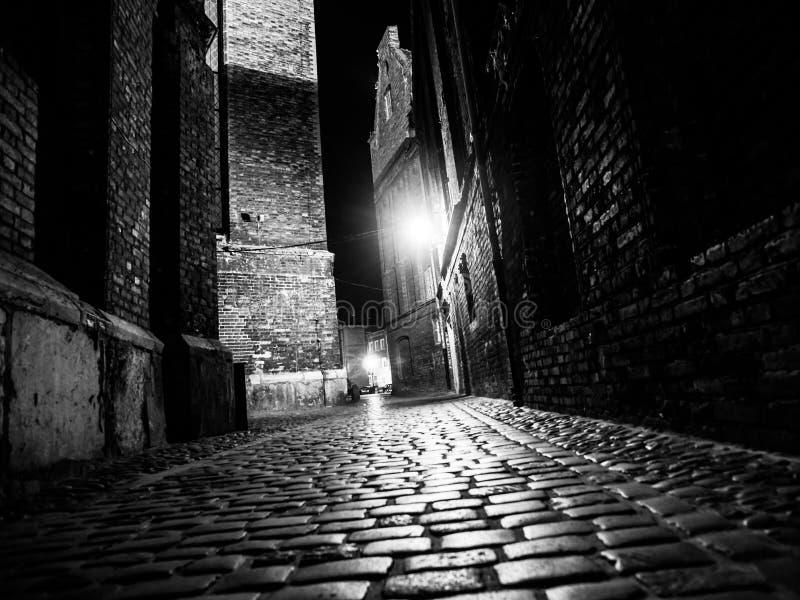 Upplyst lappad gata i gammal stad vid natt arkivbild