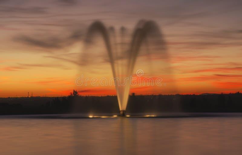 Upplyst springbrunn på skymning arkivfoton