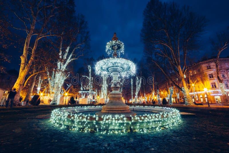 Upplyst springbrunn på Zrinjevac Zagreb, Kroatien, jul M royaltyfria bilder