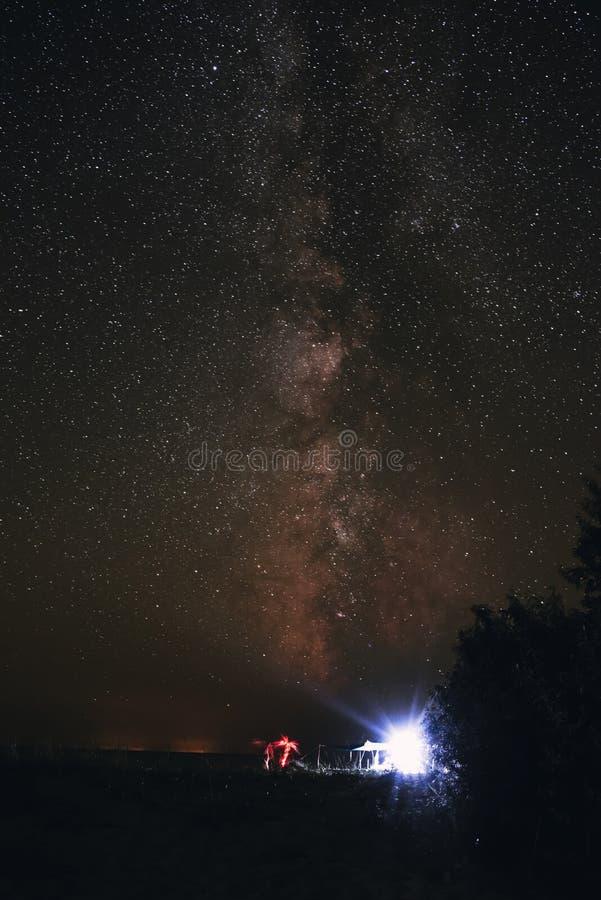 Upplyst tält på stranden mot bakgrunden av en ljus himmel med den mjölkaktiga vägen royaltyfri bild