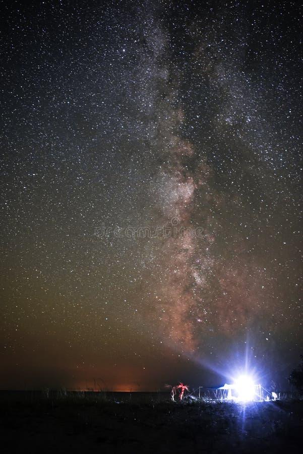 Upplyst tält på stranden mot bakgrunden av en ljus himmel med den mjölkaktiga vägen arkivbilder