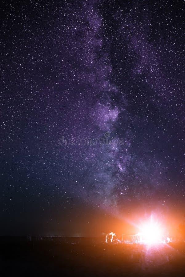 Upplyst tält på stranden mot bakgrunden av en ljus himmel med den mjölkaktiga vägen arkivfoton