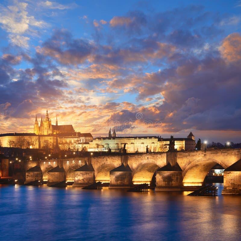 Upplysta Charles Bridge reflekteras i den Vltava floden tidigt in royaltyfria bilder