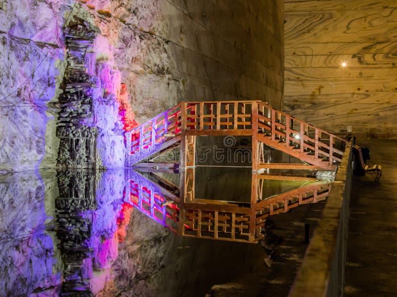 Upplysta stalaktit från den salta och träbron över behållaren i salta miner i Slanic - Salina Slanic Prahova - i royaltyfri foto