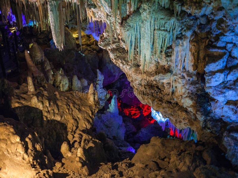 Upplysta stalaktit och stalagmit i den Ngilgi grottan i Yallingup arkivfoto