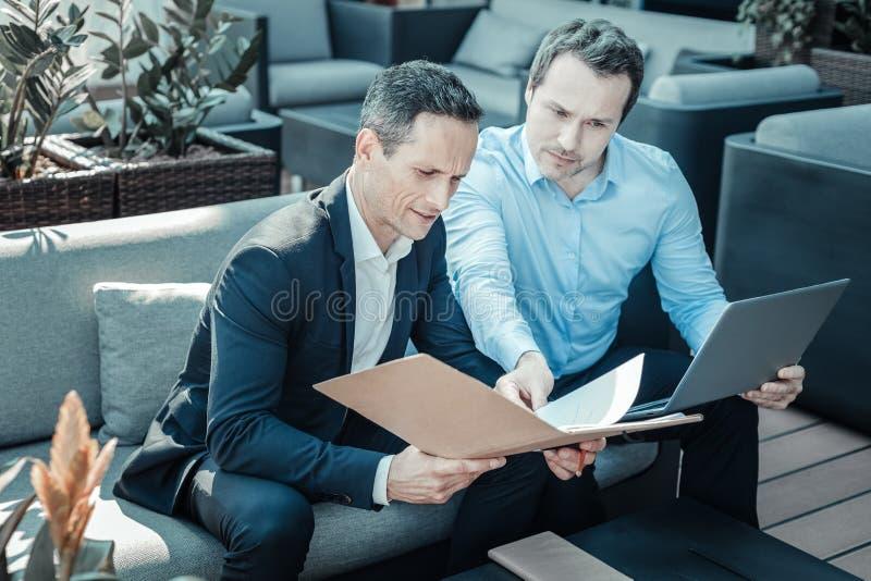Uppmärksam affärsman som läser nya dokument fotografering för bildbyråer