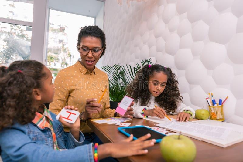 Uppmärksam angenäm barnkammarelärare som berättar gulliga förskolebarn om bokstäver royaltyfri foto