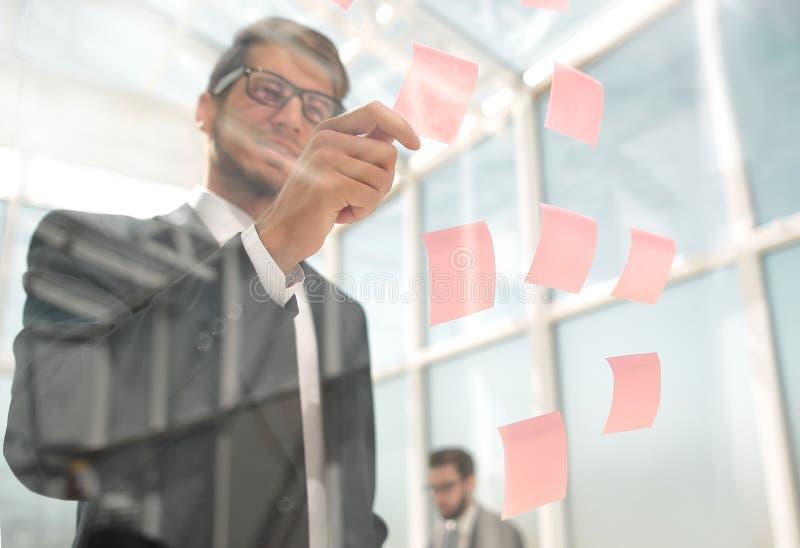 Uppmärksam anställd läser enanmärkning på kontorsbrädet arkivfoto