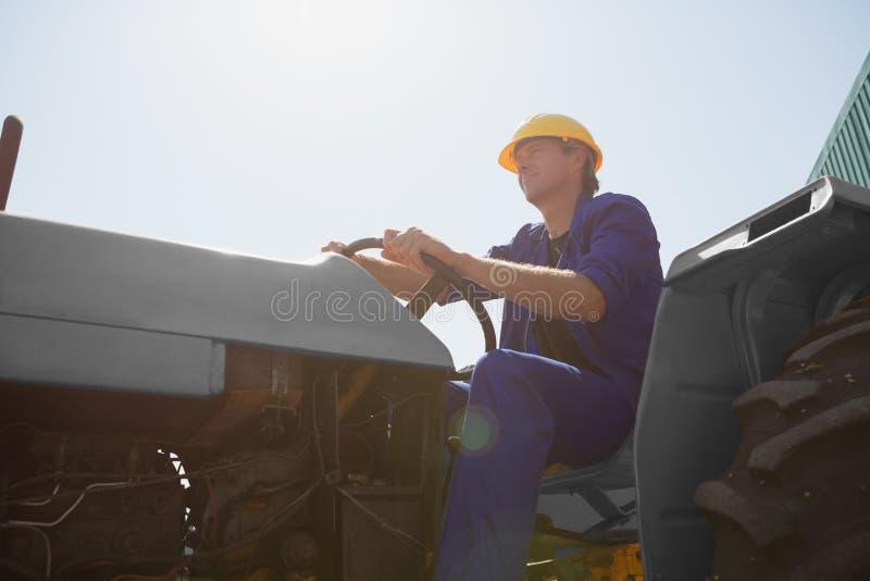 Uppmärksam arbetare som kör en traktor royaltyfri fotografi