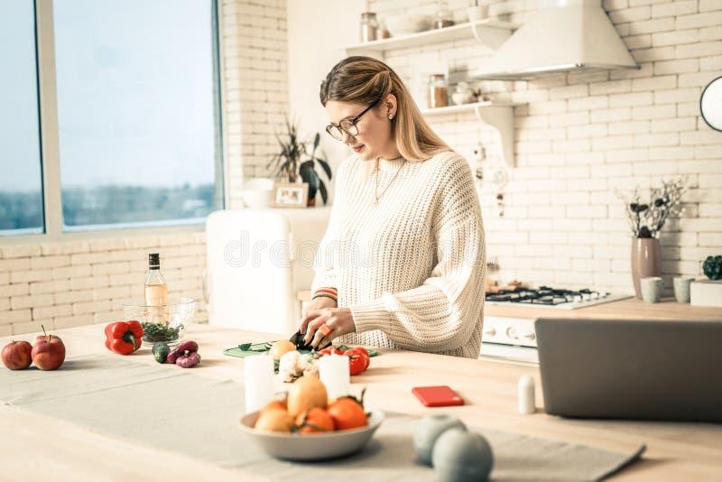 Uppmärksam arbetsam dam som skivar grönsaker under förberedelseprocess arkivfoton
