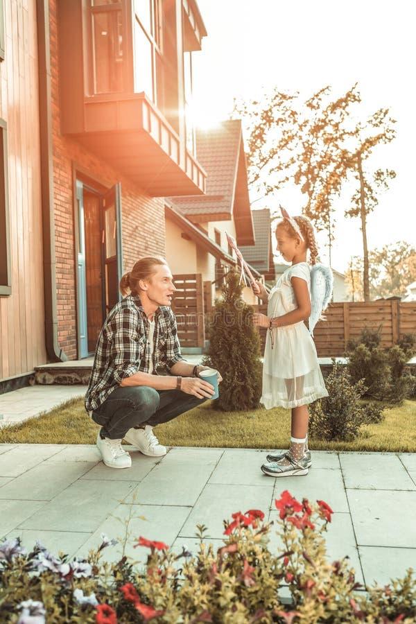 Uppmärksam blond fader som framme sitter på knä av hans dotter arkivfoton