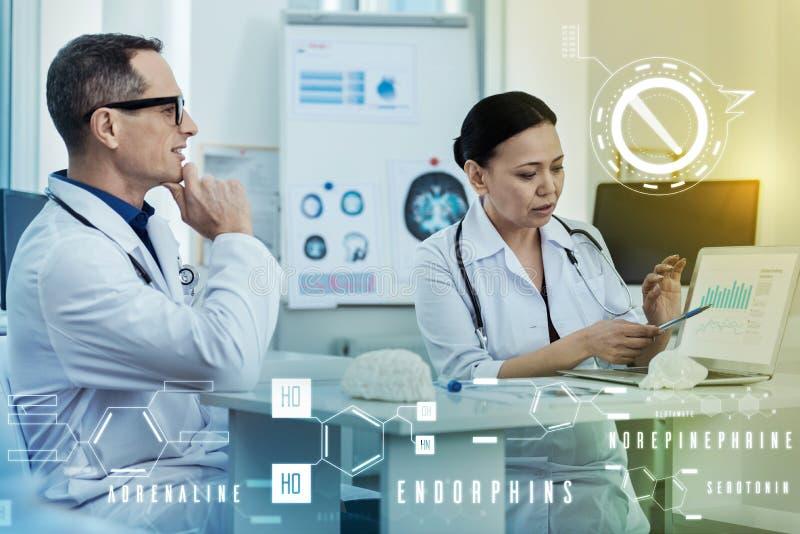 Uppmärksam doktor som pekar till skärmen och hennes coworker som ser intresserade royaltyfri bild