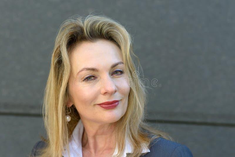 Uppmärksam eftertänksam attraktiv mogen blond kvinna royaltyfria foton