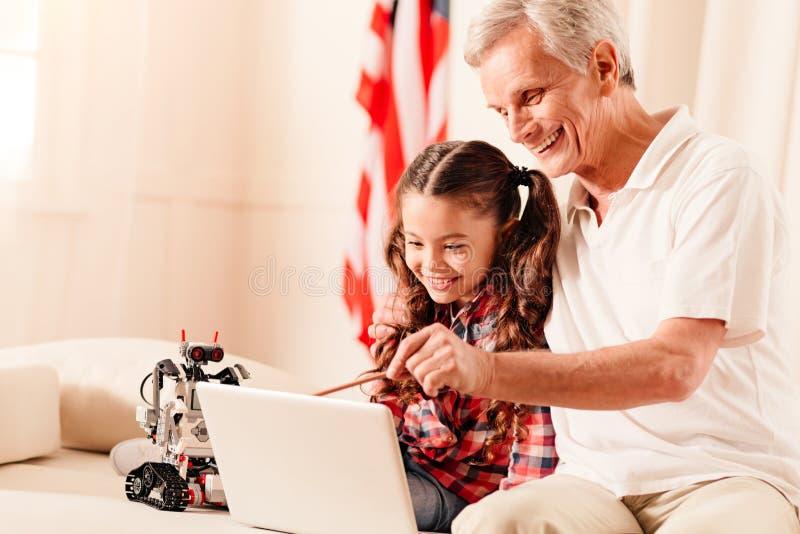 Uppmärksam farfar som berättar hans barnbarn något som roar royaltyfria foton