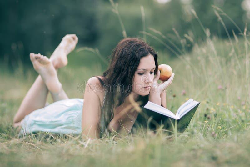 Uppmärksam flicka med äpplet som ligger på det gröna gräset och läser en bok royaltyfri bild