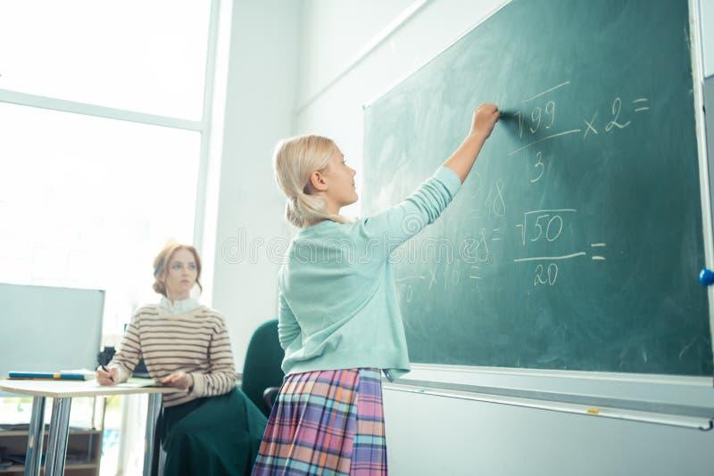 Uppmärksam flicka som arbetar på svart tavla under matematikgrupp royaltyfria foton