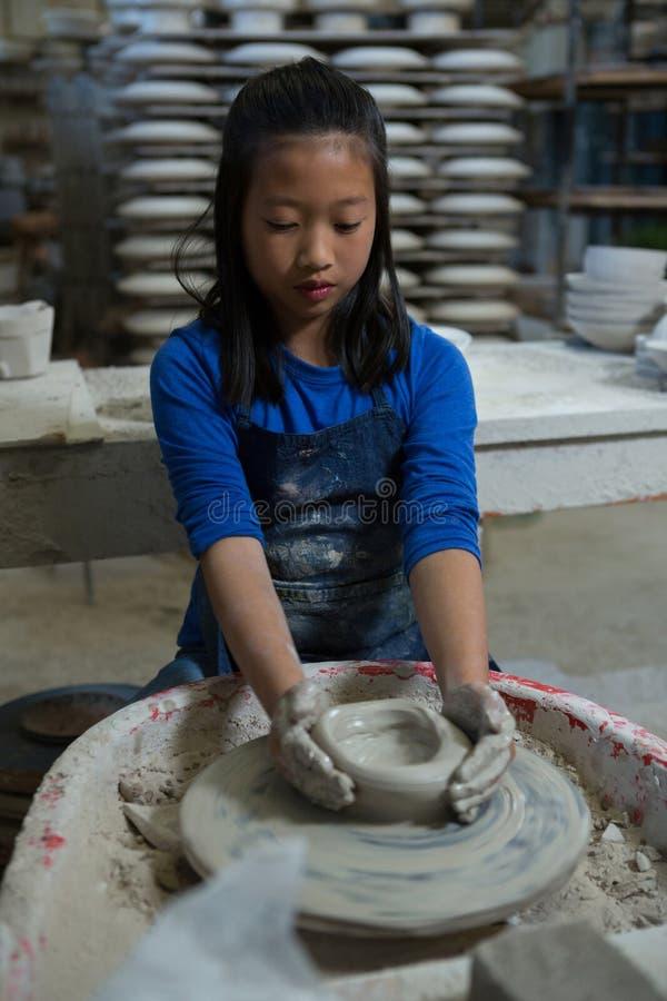 Uppmärksam flicka som gjuter en lera royaltyfri fotografi