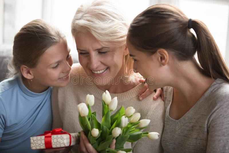 Uppmärksam fullvuxen upp dotter och sondotter som gratulerar farmodern med födelsedag royaltyfri foto