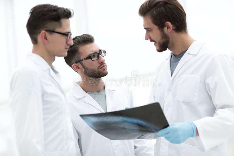 Uppmärksam grupp av doktorer som diskuterar en röntgenstråle arkivfoton