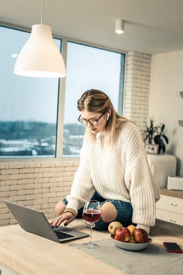 Uppmärksam kvinna i klara exponeringsglas som sitter på köksbordet och använder bärbara datorn royaltyfria bilder