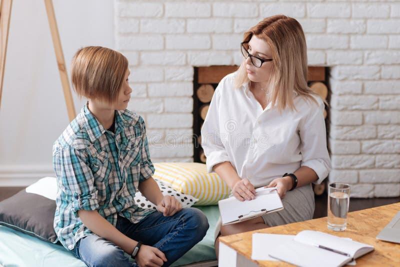 Uppmärksam kvinnapsykolog som sitter nära tonåring royaltyfri foto