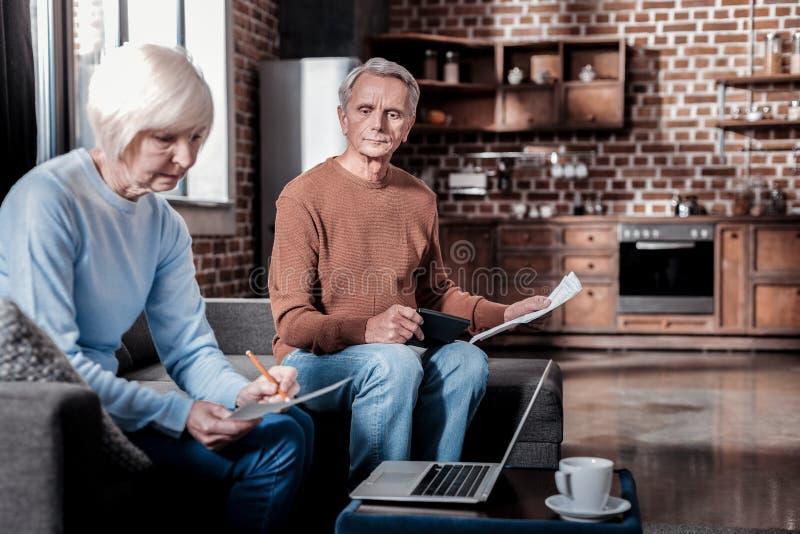 Uppmärksam kvinnlig person som räknar hennes pension fotografering för bildbyråer