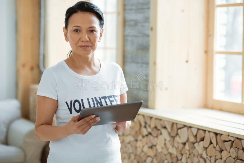 Uppmärksam kvinnlig volontär som använder minnestavlan arkivbild