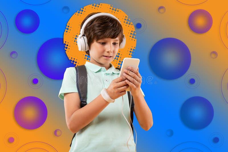 Uppmärksam lockande pojke som väljer playlisten på bakgrund arkivbild