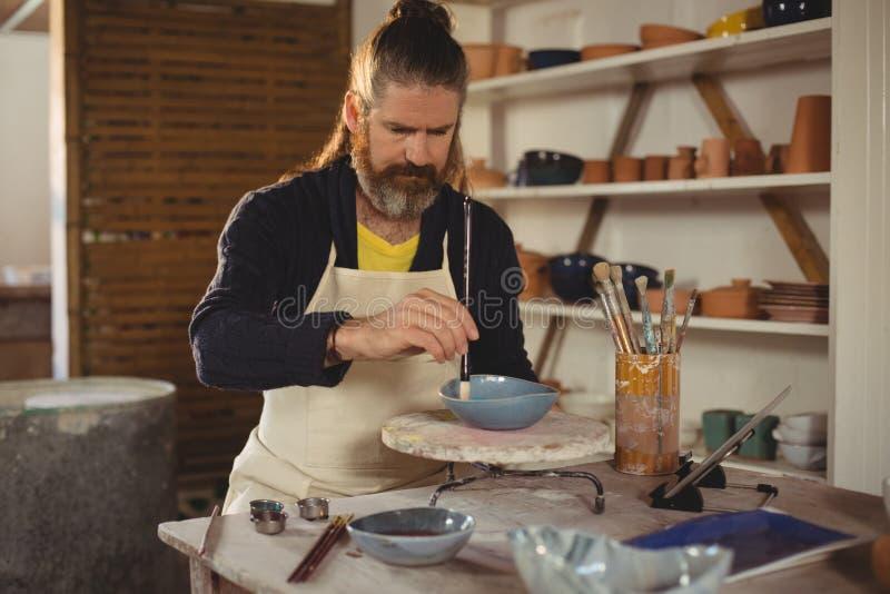 Uppmärksam manlig keramikermålning på bunken royaltyfri bild