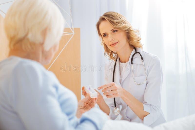 Uppmärksam pålitlig doktor som talar till hennes åldriga patient och ser vänlig arkivfoton