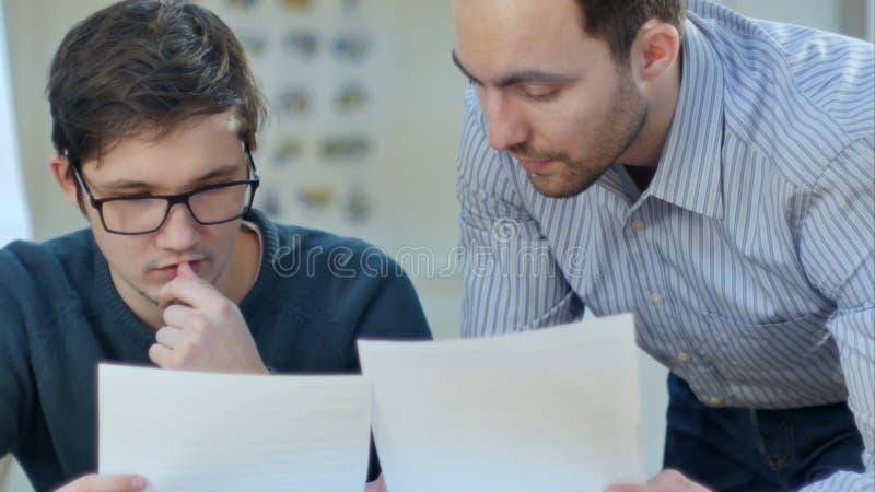 Uppmärksam pojke som studerar med en bärbar dator medan lärare som hjälper honom arkivfoto