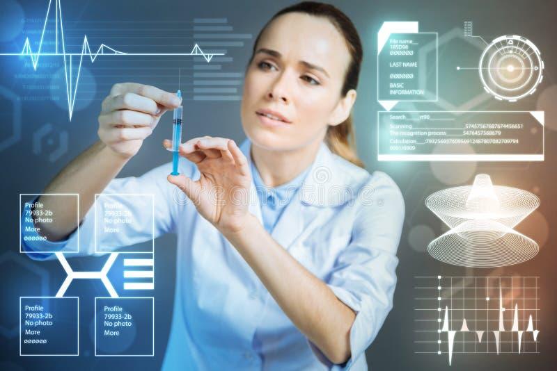 Uppmärksam sjuksköterska som ser fundersam, medan rymma en injektionsspruta royaltyfria foton