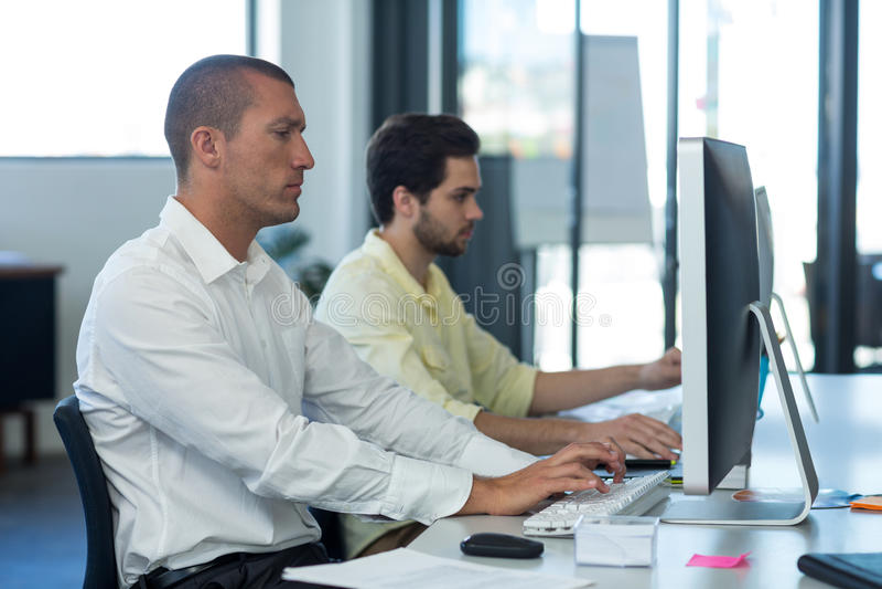 Uppmärksamma affärsmän som arbetar på persondatorn royaltyfri foto