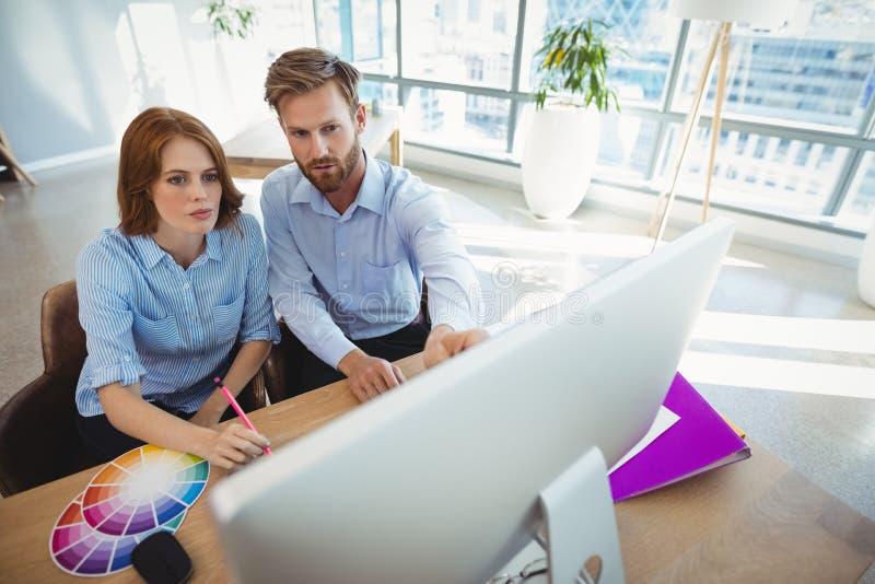 Uppmärksamma ledare som arbetar över persondatorn på skrivbordet royaltyfria foton
