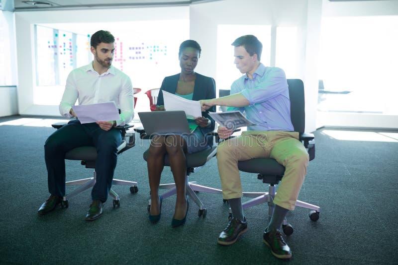 Uppmärksamma ledare som diskuterar över graf arkivbild