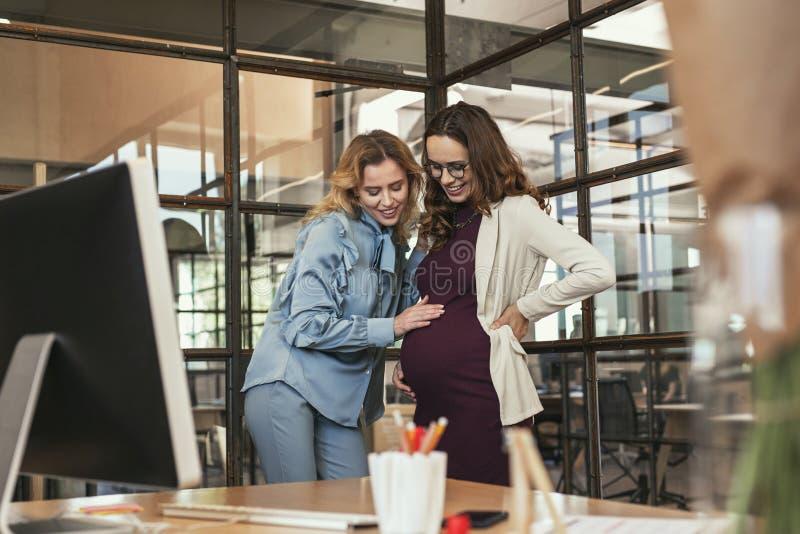 Uppmuntrande gravid kvinna för optimistisk kollega fotografering för bildbyråer