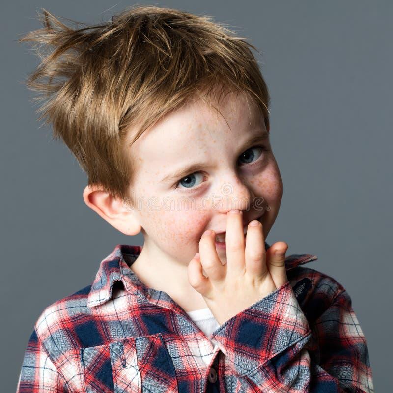 Uppnosig liten röd hårunge som väljer hans näsa för att provocera arkivbilder