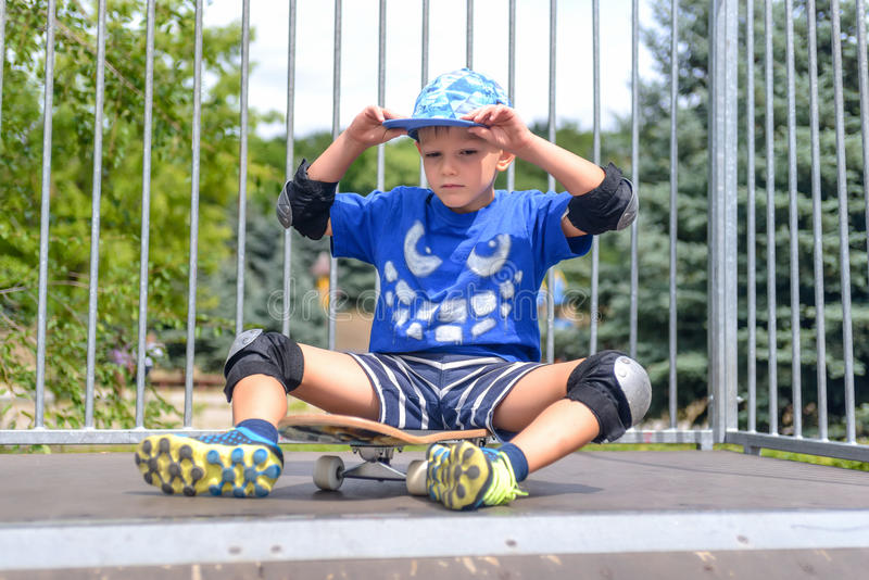 Uppnosigt ungt pojkesammanträde på hans skateboard fotografering för bildbyråer