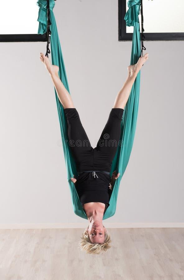 Uppochnervänd kvinna som gör flyg- yogahuvudställningar royaltyfria bilder