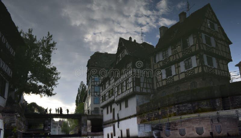 Uppochnervänd reflexionsbild av kanaler och byggnader av Strasbourg i Frankrike arkivbilder