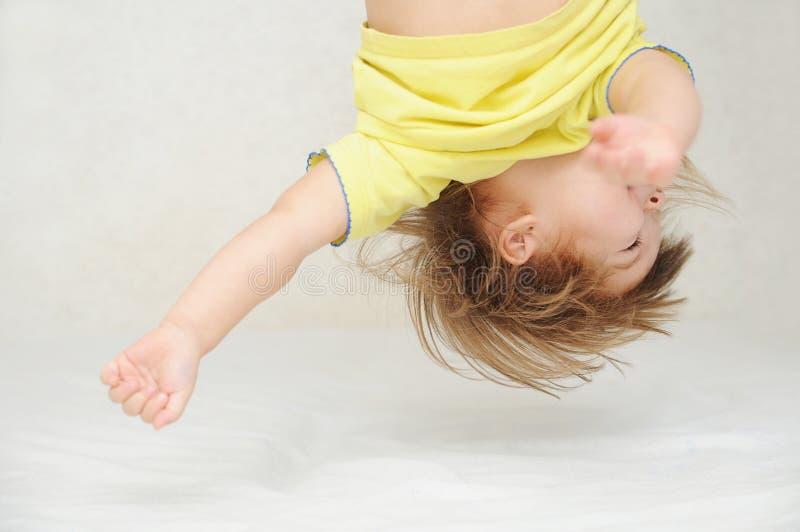Uppochnervänt huvud för lycklig rolig liten flicka som har gyckel royaltyfria foton