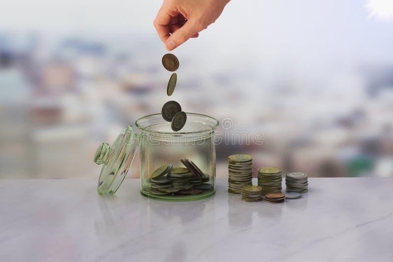 Uppochnervänt kruset av mynt och handbakgrund arkivfoton
